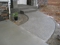 A sidewalk and step of exposed aggregate flatwork.
